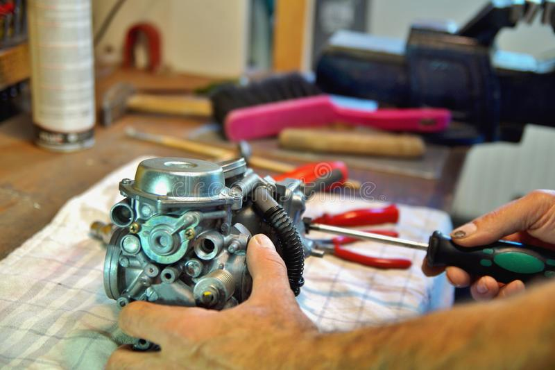 Motorcycle carburetor. Automotive Carburetor Repair. Male Using A Screwdriver To Rebuild A Carburetor On A Workbench. royalty free stock photography