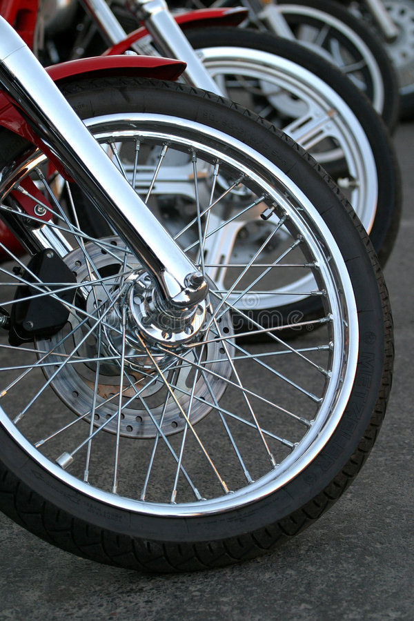 Motorcycle Chrome. A row of parked Harley Davidson motorcycles was the inspiration for this photograph of chrome wheels. Nice shapes and form. Sorry, no parking royalty free stock photography