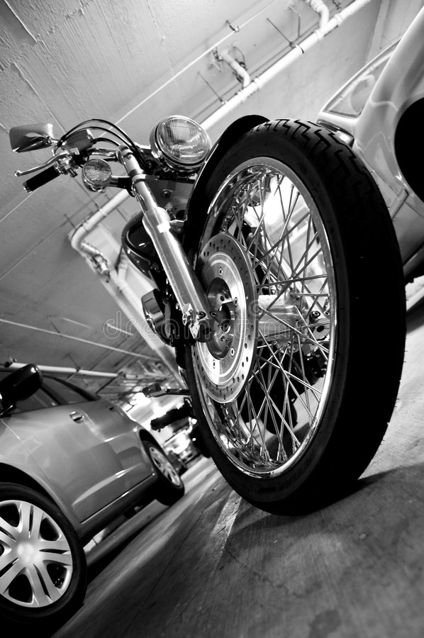 Motorcycle chrome parked. A motorcycle front wheel with chrome spokes and tire. In an underground parking structure and concrete pavement. Red tank on a road hog stock images