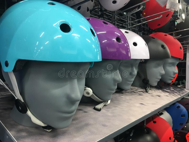 Motorcycle Colorful helmet Shop on the shelves. Multi-colored protective bike helmets in the shop. A mannequin wearing a stock image