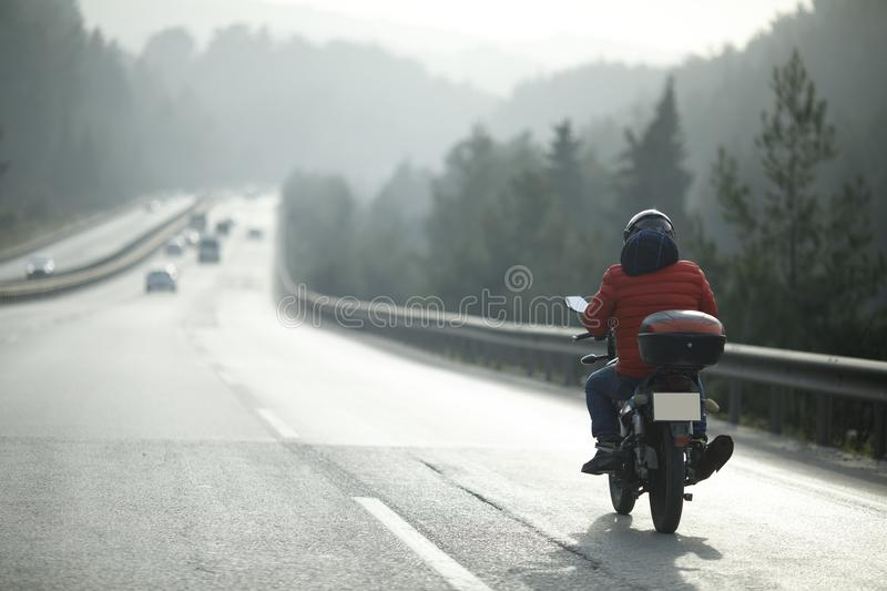 Motorcycle Courier On The Highway. Motorcycle courier on the road selective focus image royalty free stock photos