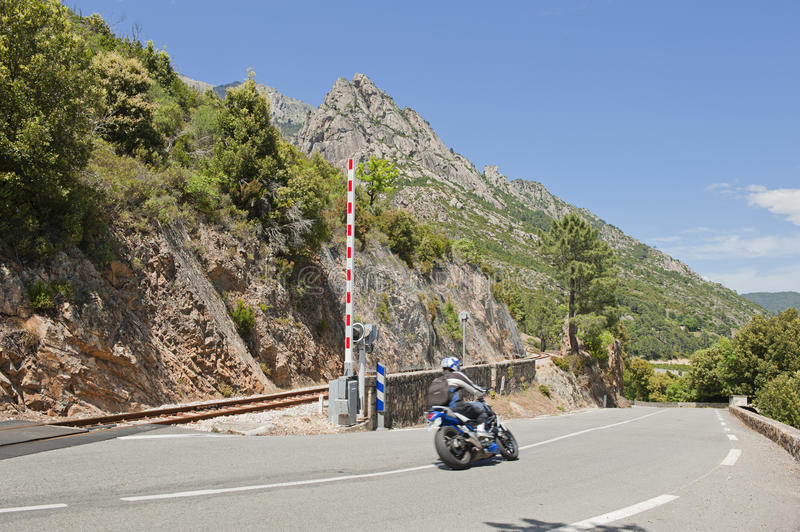 Motorcycle crossing railway track in Corsica, Fran royalty free stock images