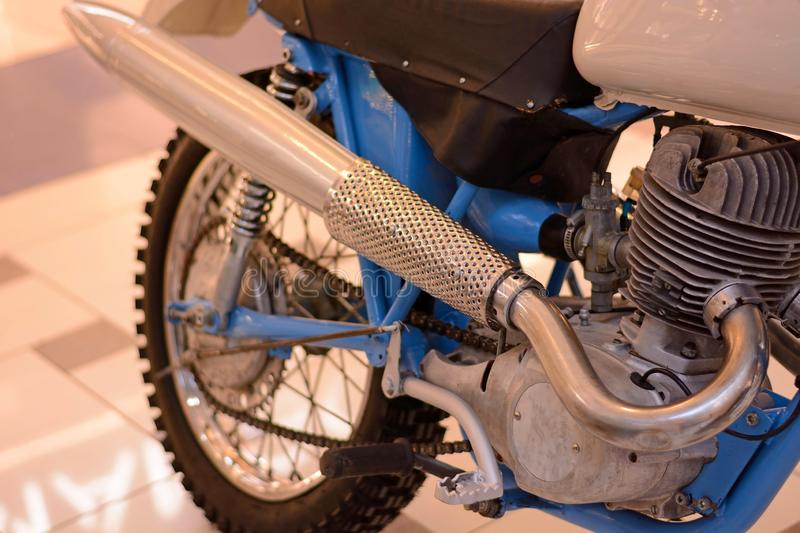 Motorcycle engine and exhaust pipe closeup. Retro bike shiny classic metal details. Gear, tube, tank, battery and carburetor stock image