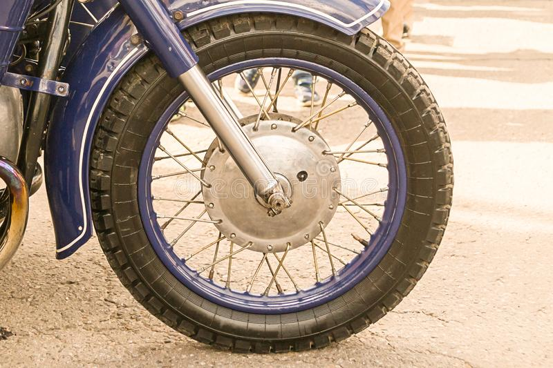 Motorcycle front wheel with shiny chrome knitting needles with blue rim close-up on the asphalt background royalty free stock photos