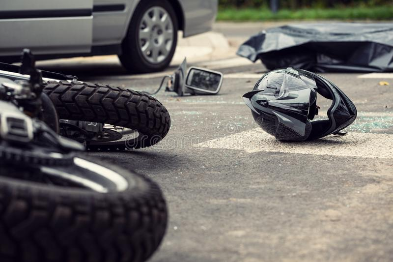 Motorcycle and helmet on the street after dangerous traffic incident royalty free stock photography