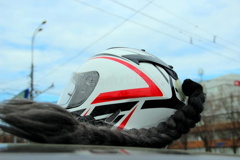 Motorcycle helmet is white with red and black stripes with black braided hair on the roof of a black car. City action to the opening of the motorcycle season royalty free stock photo