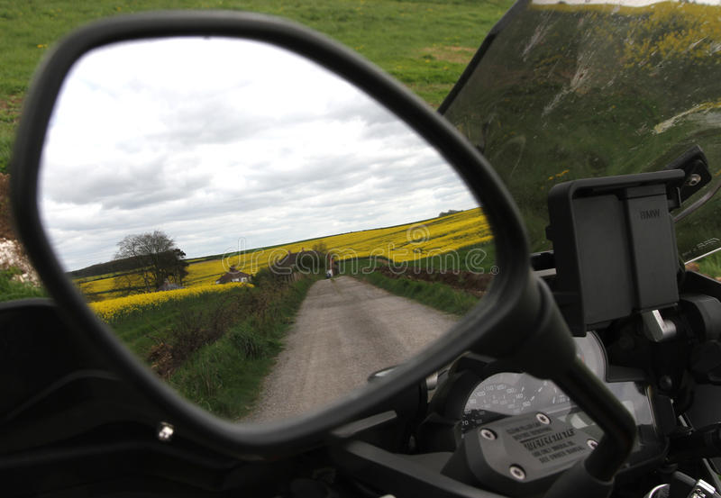 Motorcycle mirror and road. Mirror on a BMW R1200GS motorcycle showing a lane with a field and a cloudy sky stock image