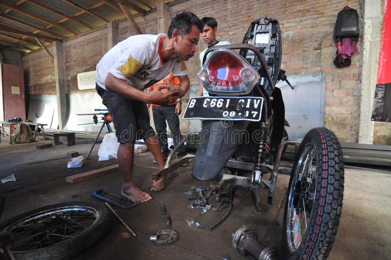Motorcycle modification for people with disabilities. Peoples with disabilities modify a motorcycle into a three-wheeler at a workshop in Klaten, Central Java stock image