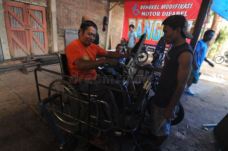 Motorcycle modification for people with disabilities. Peoples with disabilities modify a motorcycle into a three-wheeler at a workshop in Klaten, Central Java royalty free stock image