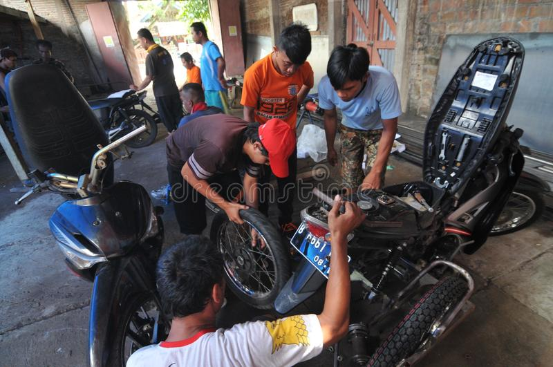 Motorcycle modification for people with disabilities. Peoples with disabilities modify a motorcycle into a three-wheeler at a workshop in Klaten, Central Java royalty free stock images
