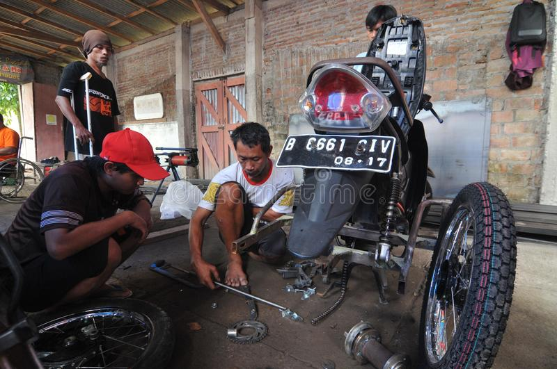 Motorcycle modification for people with disabilities. Peoples with disabilities modify a motorcycle into a three-wheeler at a workshop in Klaten, Central Java stock photos