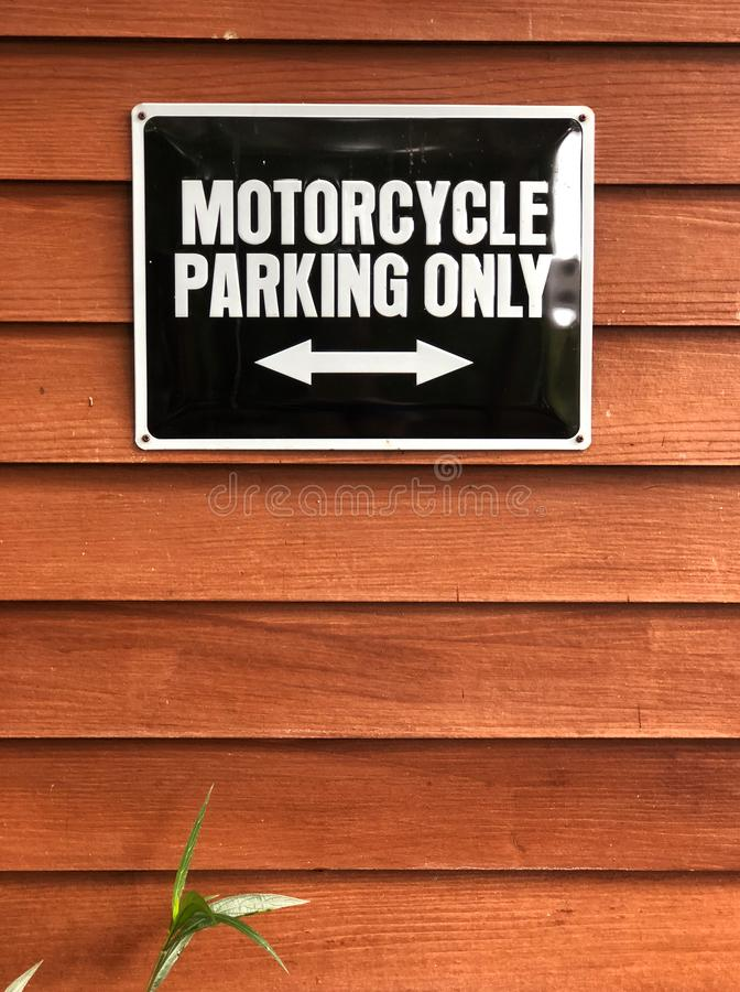 Motorcycle parking sign on wooden wall. Black sign and white color text `Motorcycle parking only` royalty free stock images