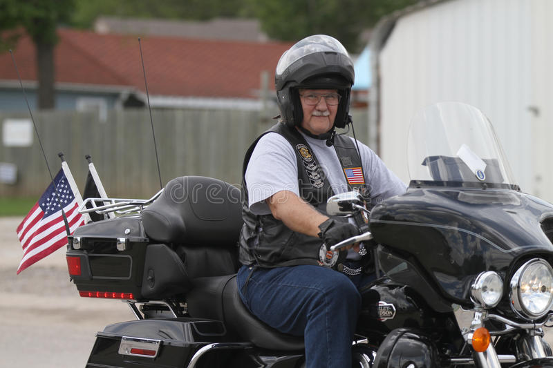 Motorcycle Poker Run Man with flags. Older man on a motorcycle with POW MIA and American Flag leaving a poker run and smiling stock photography