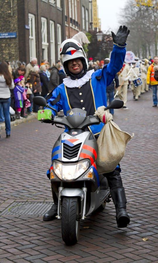 Motorcycle policeman dressed in costume waving. DORDRECHT, NETHERLANDS - NOVEMBER 18: Motorcycle policeman dressed in costume waving to the kids as escort to stock image