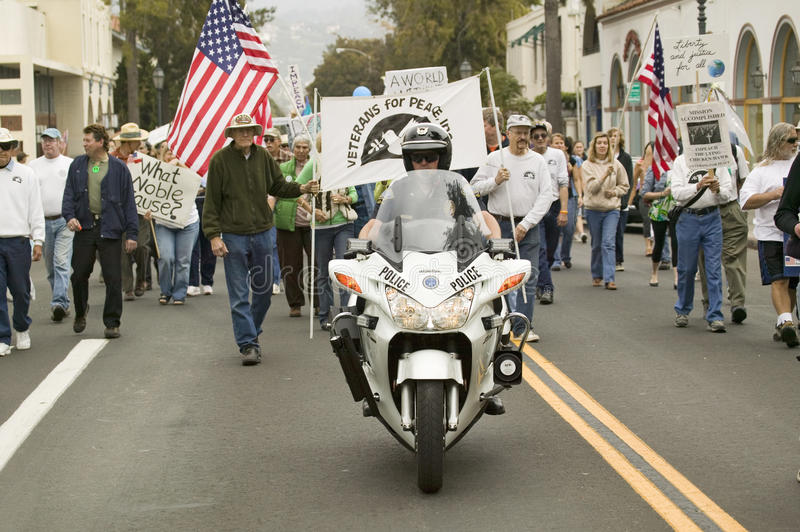 A motorcycle policeman leads parade of protesters against George W. Bush and the Iraq War at an anti-Iraq War protest march in San royalty free stock photos