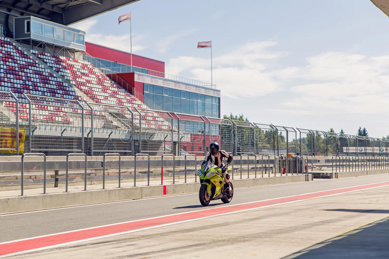 Motorcycle racer in a green suit and helmet, riding a motorcycle around the pits to practice stock photo
