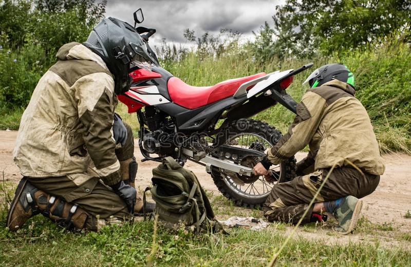 Motorcycle repair on the road. Two men in motorcycle gear checking rear wheel of dirtbike. Adjusting bolt with socket wrench on bike. Riders fixing motorbike stock image