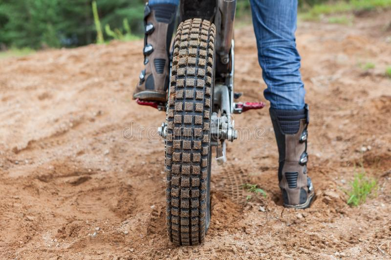 Motorcycle rider has a ride in sand pit, rear view of bike tire and men boots. Motorcycle male rider has a ride in sand pit, rear view of bike tire and man boots royalty free stock image