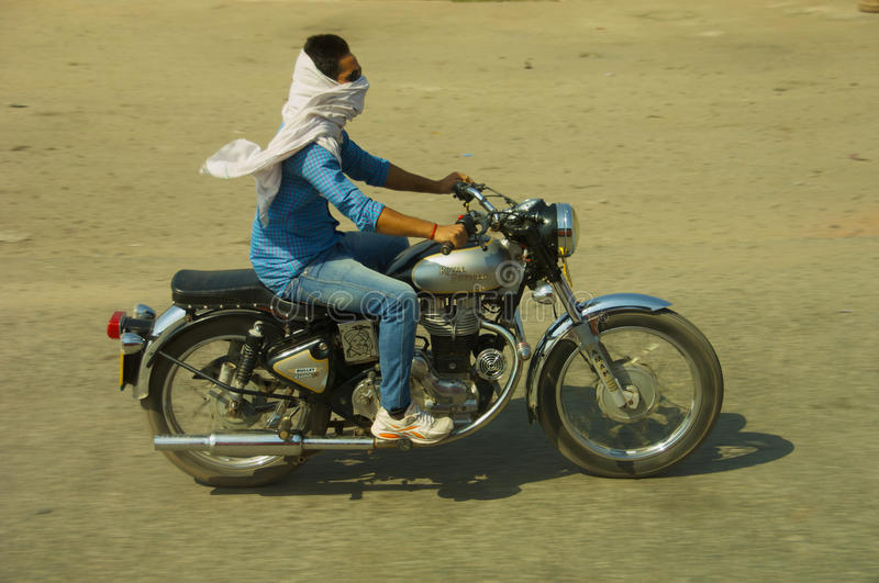 Motorcycle rider India. Man riding Royal Enfield motorbike up the Indian highway stock photography