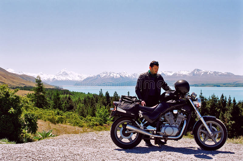 Motorcycle rider near mountain and lake. A motorcyclist and his bike with Mount Cook in the background, New Zealand royalty free stock images