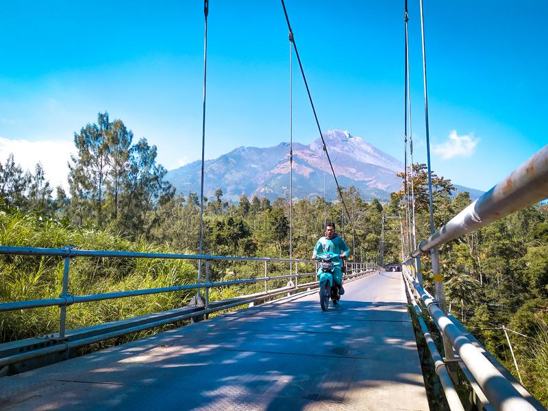 Motorcycle riders walk over the suspension bridge stock photos