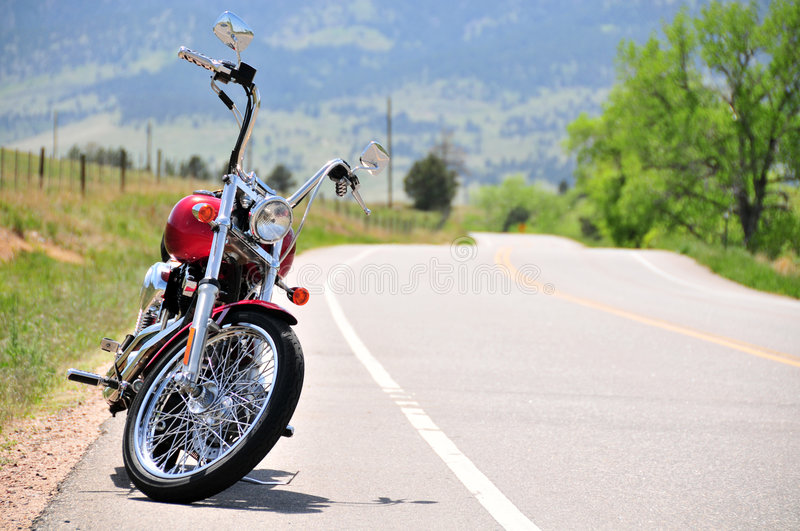 Motorcycle on secluded road. Motorcycle parked on a secluded road in the sun stock image