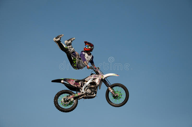 Motorcycle stunt man. A professional motorcycle rider performs stunts in a mid air jump