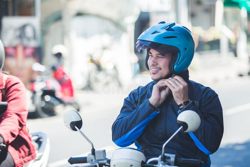 Motorcycle taxi driver fastening his helmet for safety riding. Portrait of motorcycle taxi driver fastening his helmet for safety riding on the side of the road stock photography