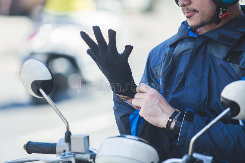 Motorcycle taxi driver wearing his gloves for safety riding. Close up portrait of motorcycle taxi driver wearing his gloves for safety riding royalty free stock photo