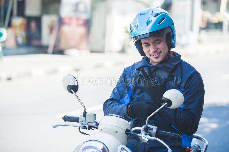 Motorcycle taxi driver wearing his gloves for safety riding. Portrait of motorcycle taxi driver wearing his gloves for safety riding on the side of the road royalty free stock images