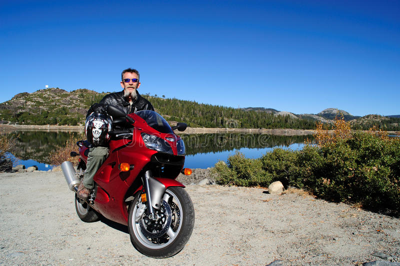 Motorcycle To The Lake. Older man stops at a mountain lake after a long motorcycle ride in the California Sierra Mountains stock photos