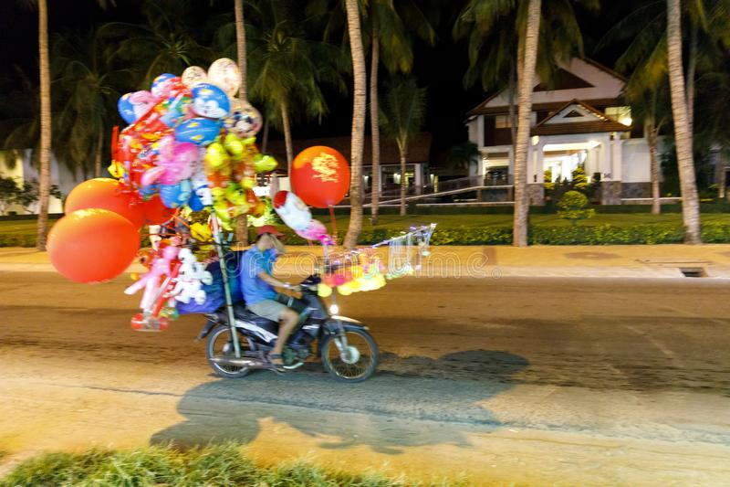 Motorcycle transport colorful balloons at night in Nam Tien, Vie stock photo