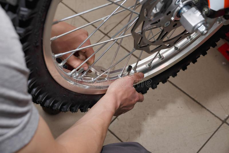 Motorcycle wheel repair after tire leaks or disc damage. Modification of certain parts of a motorcycle when it is used for a certain period of time by an royalty free stock images