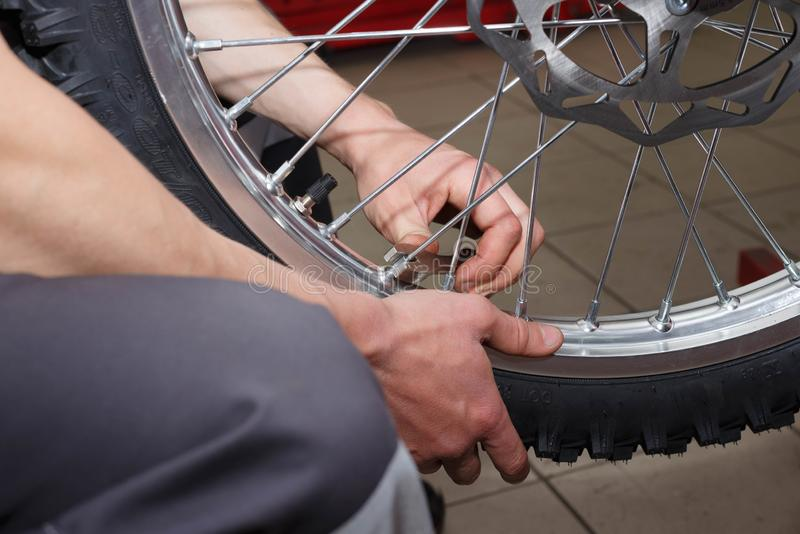 Motorcycle wheel repair after tire leaks or disc damage. Modification of certain parts of a motorcycle when it is used for a certain period of time by an stock photo