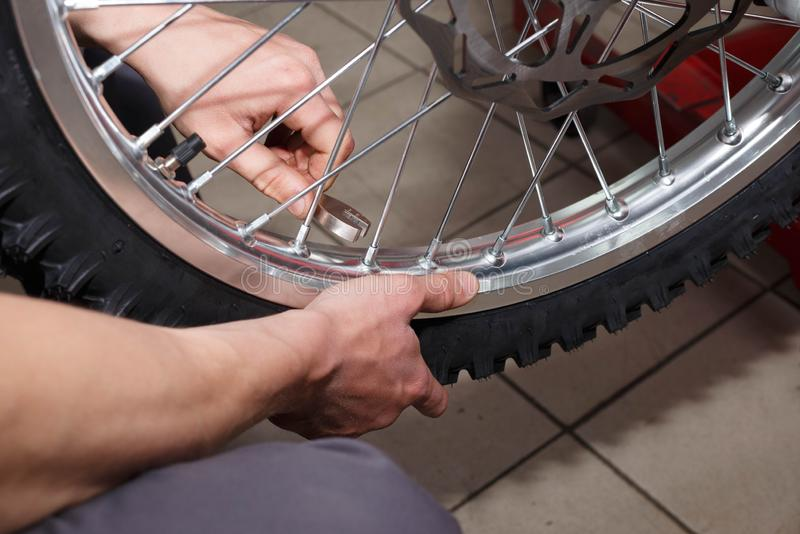 Motorcycle wheel repair after tire leaks or disc damage. Modification of certain parts of a motorcycle when it is used for a certain period of time by an royalty free stock photos