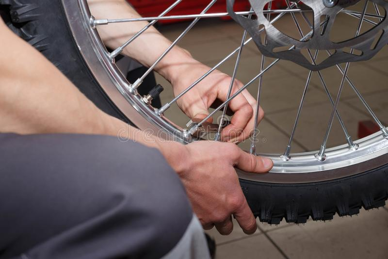 Motorcycle wheel repair after tire leaks or disc damage. Modification of certain parts of a motorcycle when it is used for a certain period of time by an stock image