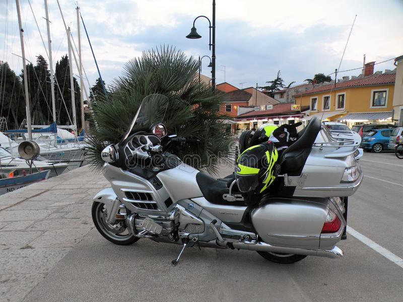Motorcycles with lighted lights stand in line with stones paved in the coastal town of Croatia, right next to the Adriatic Sea.In stock photos