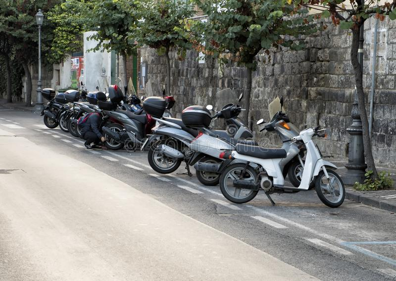 Motorcycles parked on a narrow street in Sorrento, Italy. Pictured are motorcycles parked on a narrow street in Sorrento, Italy. The motorcycle is a popular mode stock photography
