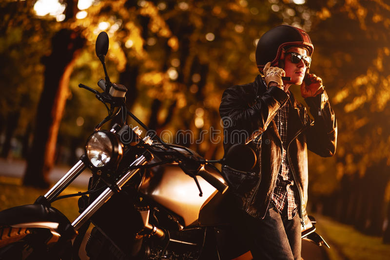 Motorcyclist with a cafe-racer motorcycle. Outdoors stock image