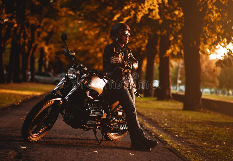 Motorcyclist with a cafe-racer motorcycle. Outdoors stock photography
