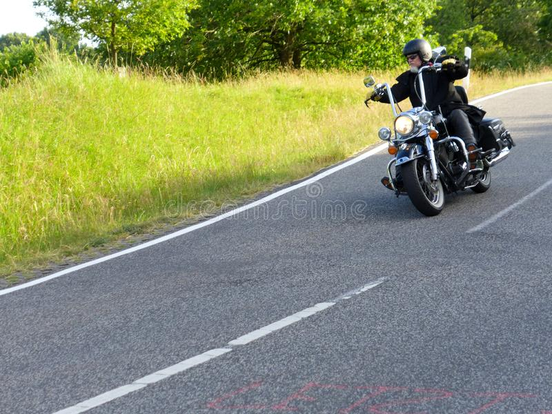 Motorcyclist goes downhill 1 royalty free stock photography