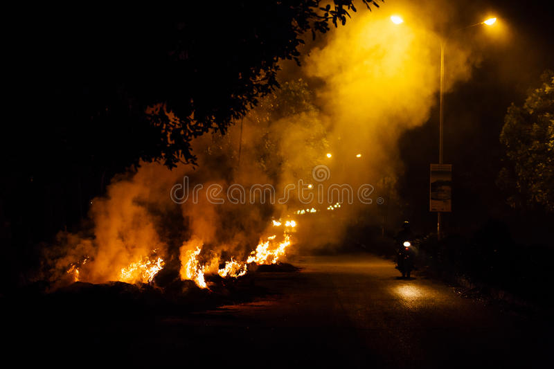 Motorcyclist goes up in smoke at night by burning garbage stock images