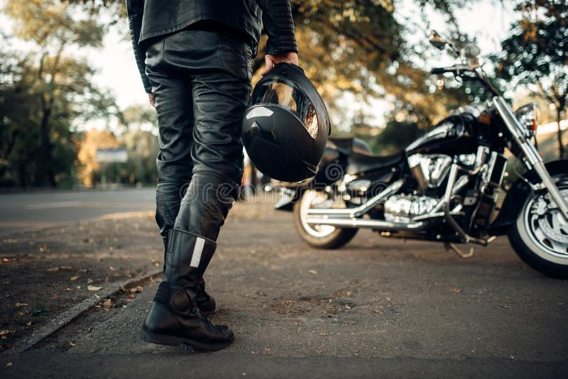 Motorcyclist with helmet in hand goes to chopper royalty free stock images