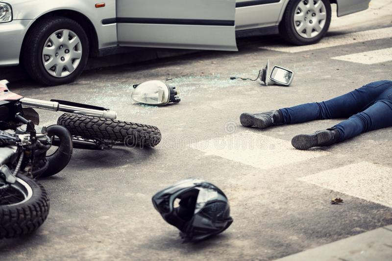 Motorcyclist helmet and motorbike on the street after collision royalty free stock photography
