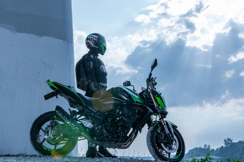 Motorcyclist in a helmet and in a protective suit stands under the bridge stock images