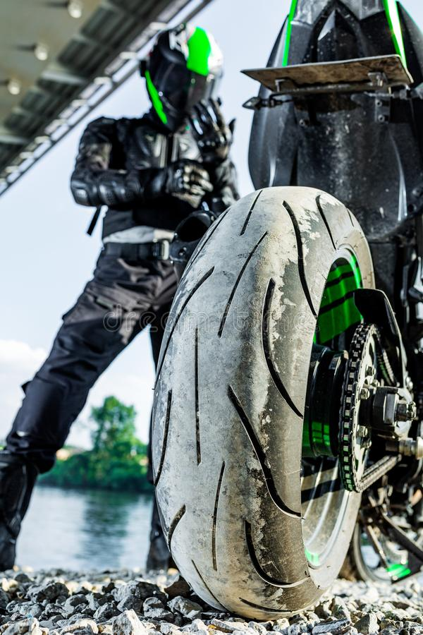 Motorcyclist in a helmet and in a protective suit stands under the bridge stock image