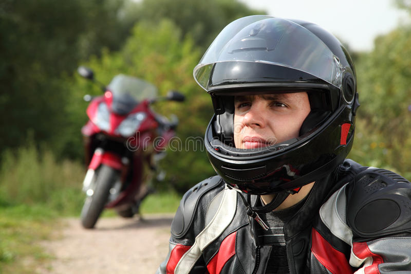 Motorcyclist and his bike on country road royalty free stock photo