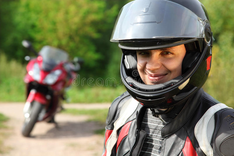 Motorcyclist and his bike on country road royalty free stock image