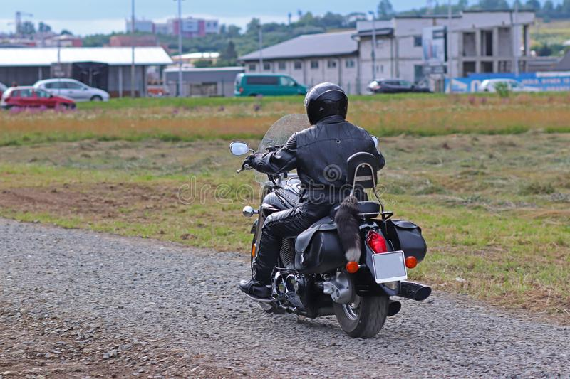 A motorcyclist in leather outfit rides a chopper on a dirt road along a dirt road against a backdrop of urban infrastructure. Hobb stock image