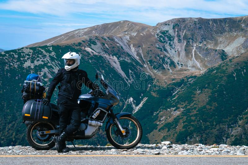 Motorcyclist man and Adventure Motorbike on the top of the mountain. Motorcycle trip. World Traveling, Lifestyle Travel vacations. Sport outdoor concept, copy stock images